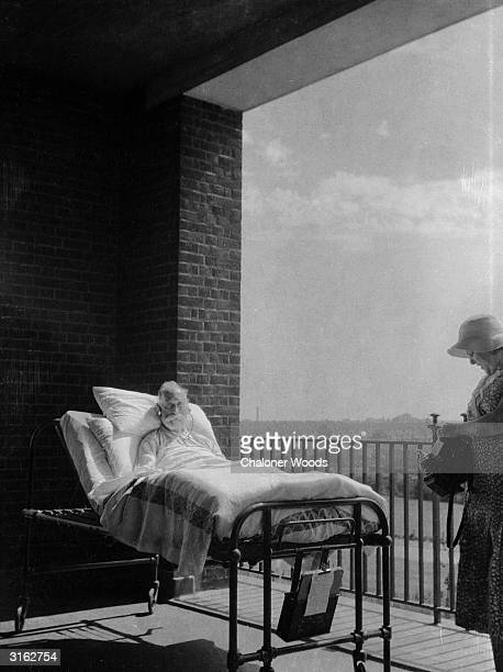 An elderly patient convalesces with his hospital bed on a balcony in order to speed his recovery with healthy fresh air