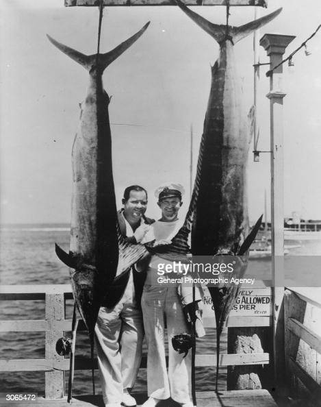 Comedy stars Oliver Hardy and on right Stan Laurel with Marlin they have caught while big game fishing