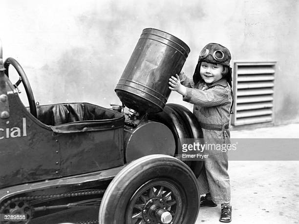 Davey Lee a child actor famous in the early 30's is standing behind his own miniature car which is an exact replica of a 'Barney Oldfield' and runs...