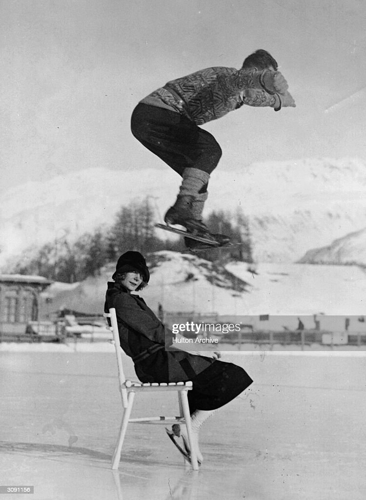 English skater Phil Taylor performing a daring leap over Freda Whitaker as she sits on a chair on the ice at St Moritz.