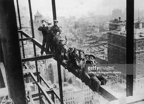 Harmonica playing steel workers perched on a girder on the 22nd storey of the Murray Hill building New York
