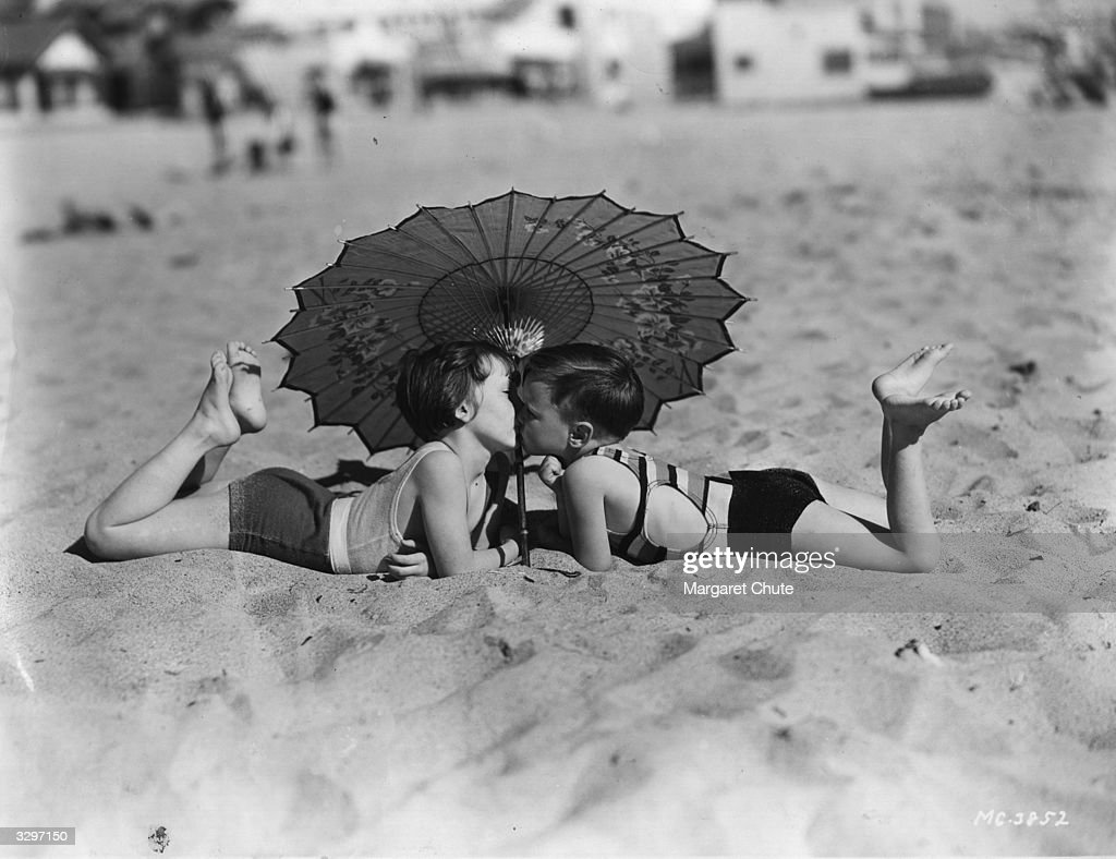 Mary Ann Jackson and Wheezer, two of the child stars of Hal Roach's 'Our Gang' comedy team seen kissing on the beach at Santa Monica during the making of a film.