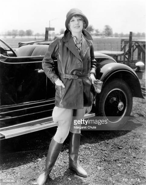 MGM actress Anita Page poses in costume for her latest role as an aviatrix She is standing in front of a large convertible car