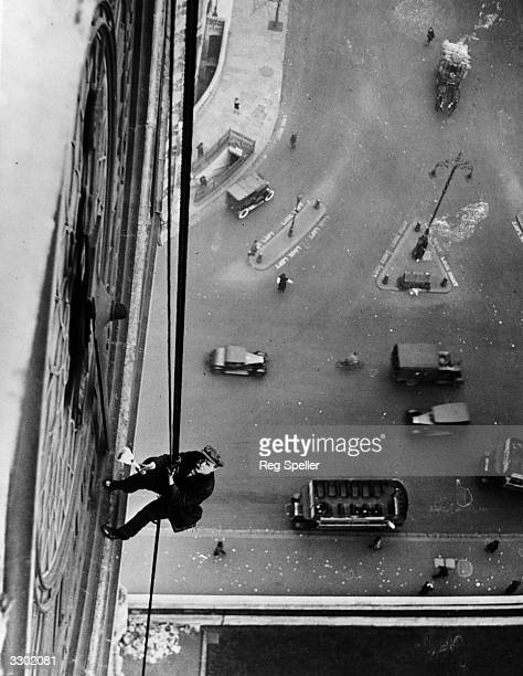 Mr Larkin suspended on ropes cleans the face of Big Ben Clock Tower Houses of Parliament London
