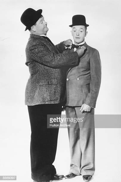Oliver Hardy adjusts his partner Stan Laurel's tie