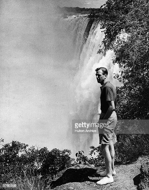 The Duke of Kent standing on a rock next to a large waterfall