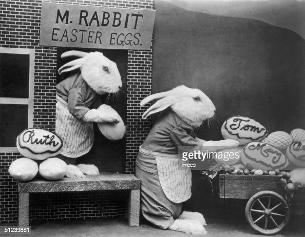 Circa 1930 Two stuffed rabbits in aprons load labelled Easter eggs from M Rabbit's store onto a small cart