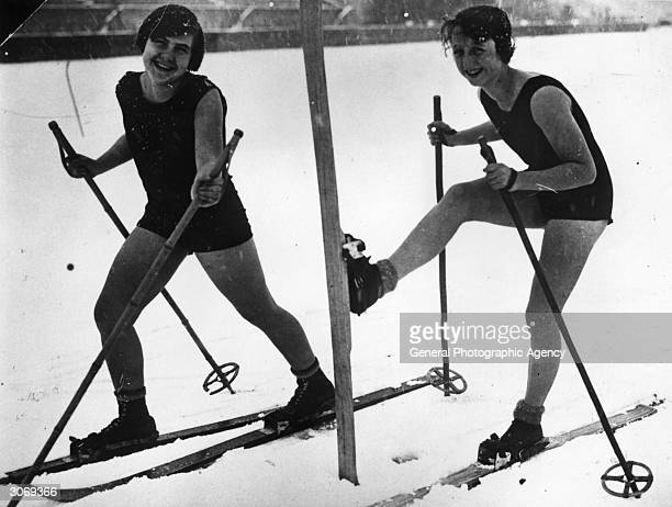 Two women in swimsuits venture out into the snow on a pair of skis