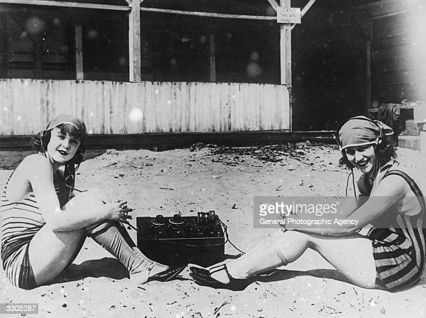 Two women listening to a BBC studio broadcast on the beach