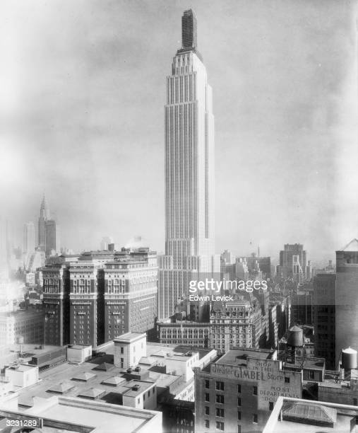 View of the Empire State Building with the top tier still under construction Manhattan New York City The Chrysler Building is visible at left An...