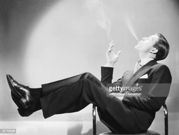 Welshborn actor Ray Milland lounges sideways in a chair smoking a cigarette