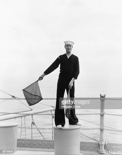 American actor Robert Montgomery practicing semaphore signals for a scene in the film 'Shipmates' directed by Harry A Pollard for MGM