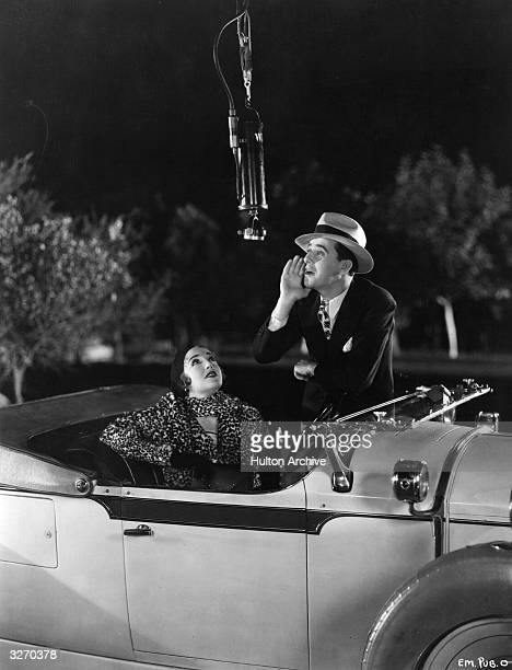 American actress Bebe Daniels with her husband Ben Lyon who is shouting into a microphone during filming