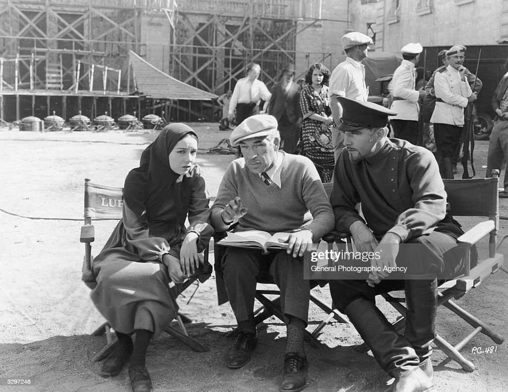 Director Edwin Carewe centre consults with actors Lupe Velez and John Boles prior to a take for the Universal film 'Resurrection' Carewe had already...