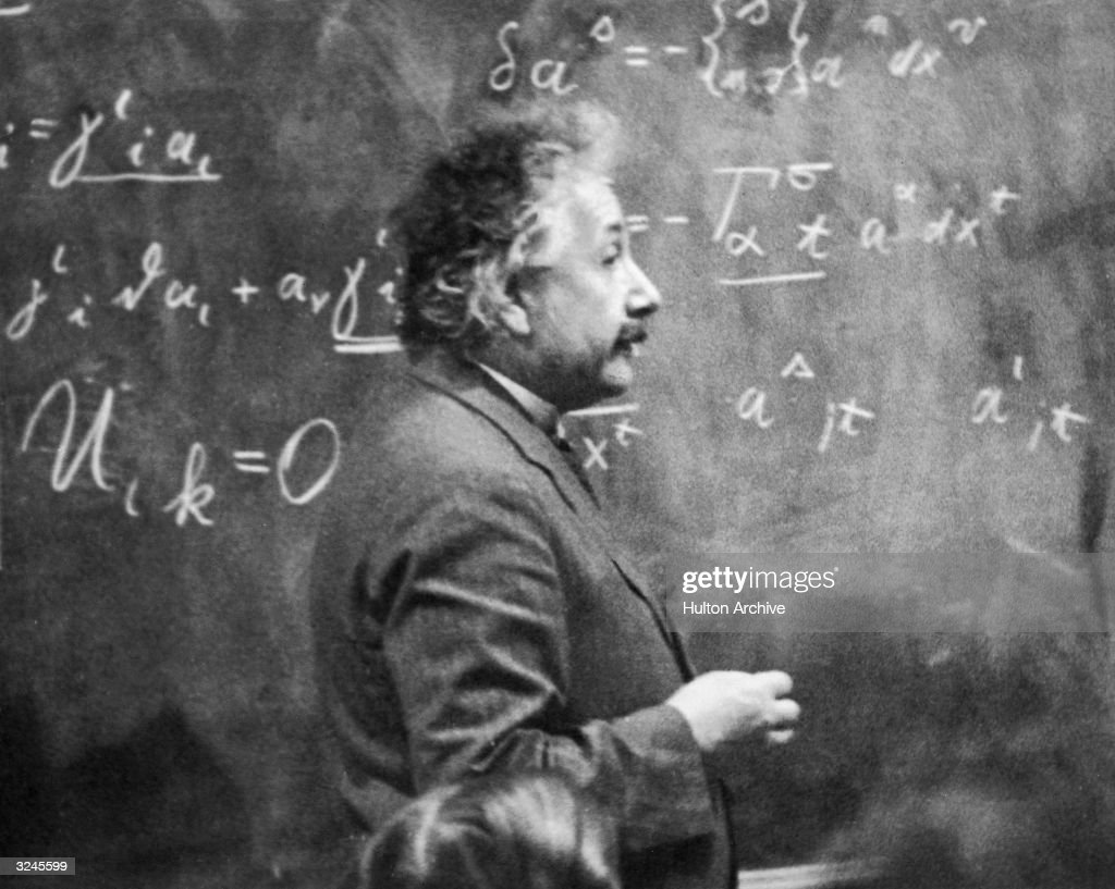 German-born physicist <a gi-track='captionPersonalityLinkClicked' href=/galleries/search?phrase=Albert+Einstein&family=editorial&specificpeople=70023 ng-click='$event.stopPropagation()'>Albert Einstein</a> (1879 - 1955) standing beside a blackboard with chalk-marked mathematical calculations written across it.