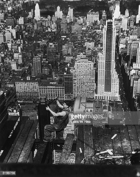 High angle view of a construction worker in overalls working on a narrow wooden beam on the 86th floor of the Empire State Building during its...