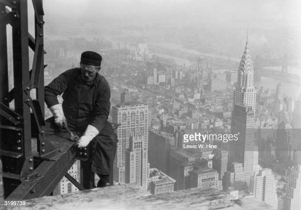 Male construction worker using a wrench on the corner of a steel beam high above the city during the construction of the Empire State Building New...