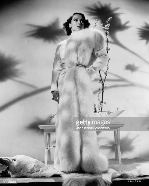 Mexican film star Dolores Del Rio stands on a polar bear skin rug in a furtrimmed coat
