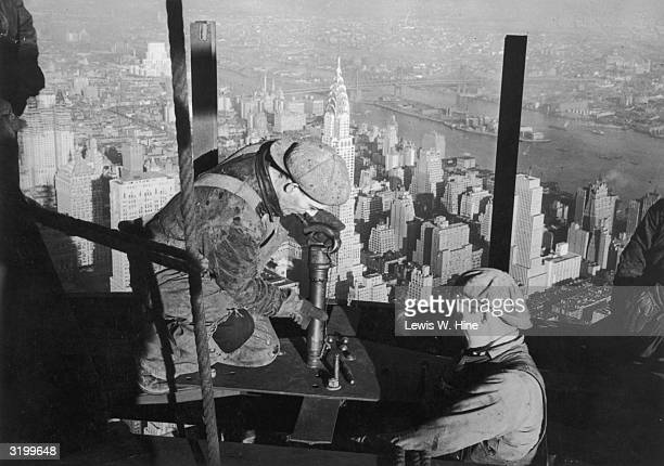 Two construction workers riveting a steel girder on top of the mooring mast of the Empire State Building during its construction New York City
