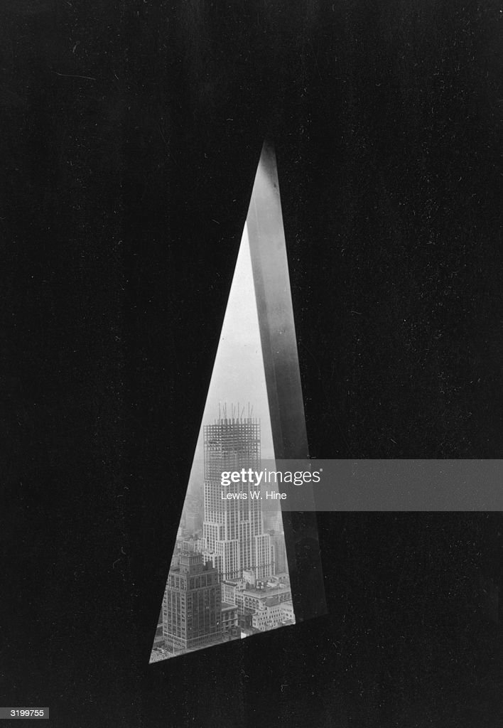 View of the Empire State Building under construction, New York City, taken through a triangular opening in the pinnacle of the Chrysler Building.