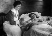 A nurse working for the American Red Cross Home Service checks her thermometer as a woman and her baby lay in their bed