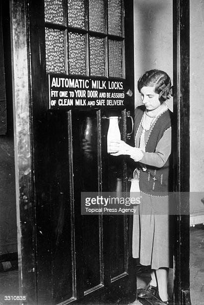 A woman unhooking a bottle of milk from an automatic milk lock which was one of the exhibits at the Exhibition of Inventions at Central Hall...