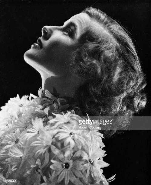American actress Katharine Hepburn wearing a dress decorated with flowers for her role in her second film 'Christopher Strong'