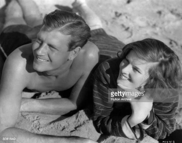 Hollywood film star Katharine Hepburn relaxes on the beach with American actor Joel McCrea