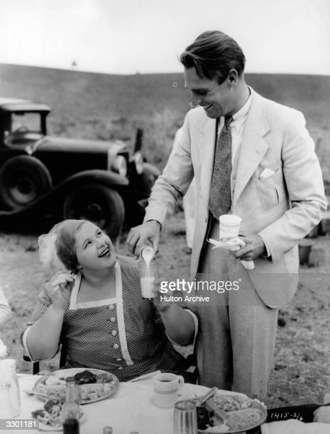 Randolph Scott and Kate Smith taking refreshments during the production of 'Hello Everybody' The film was directed by William Seiter for Paramount
