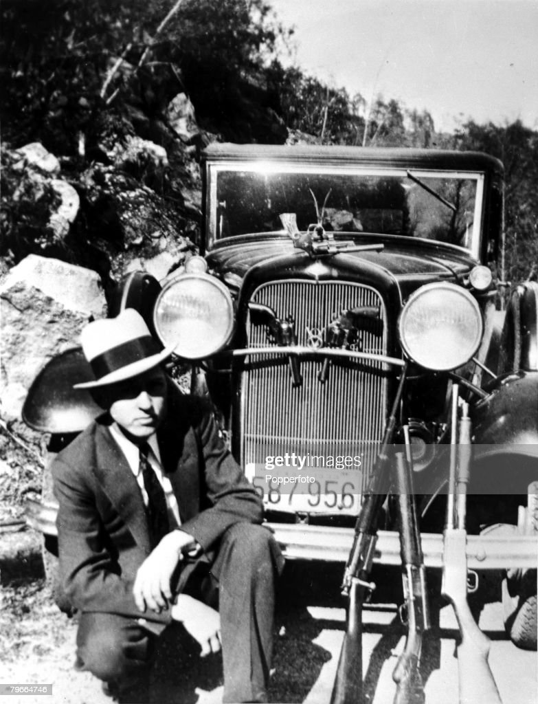 Circa 1932, USA, American criminal Clyde Barrow who together with girlfriend Bonnie Parker of 'Bonnie and Clyde' infamy from August 1932 until being betrayed and killed by Police in May 1934, Note the wide array of hand guns and rifles in his arsenal