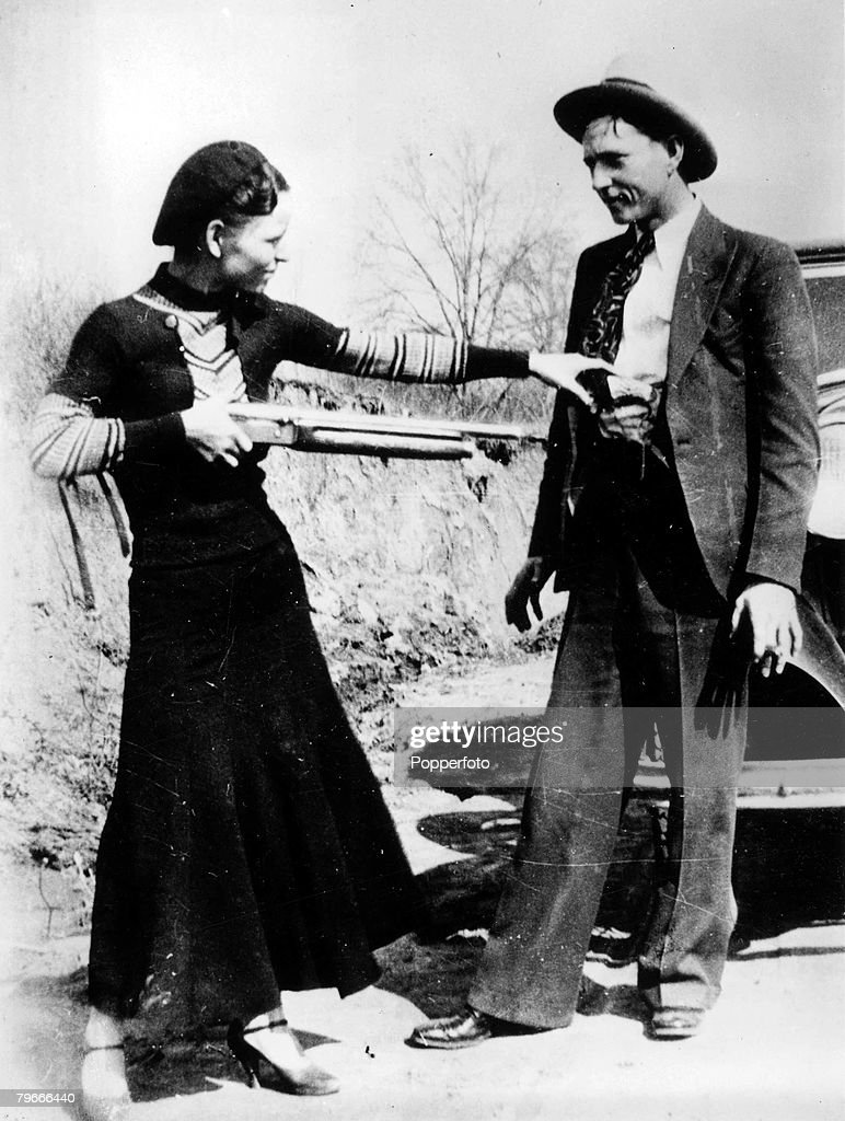 Circa 1932, USA, Bonnie Parker points a shotgun at boyfriend Clyde Barrow, together they found infamy as ,Bonnie and Clyde from August 1932 until they were killed at a Police roadblock by Police in May 1934, Despite their popular romantic image, they and their gang were responsible for a number of murders
