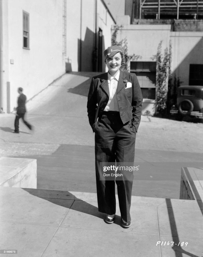 A casual Marlene Dietrich (1901 - 1992) dressed in slacks, jacket and hat smiles in the sunshine with her hands in her pockets.
