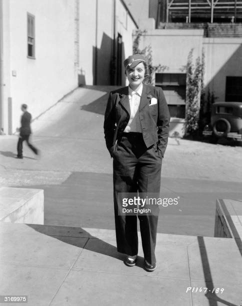 A casual Marlene Dietrich dressed in slacks jacket and hat smiles in the sunshine with her hands in her pockets