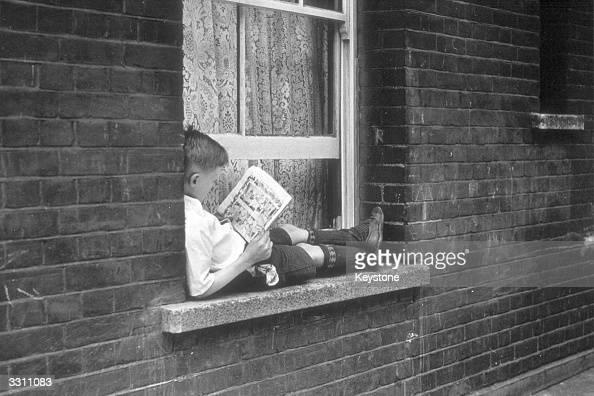 A young boy lying on a window ledge reading a comic