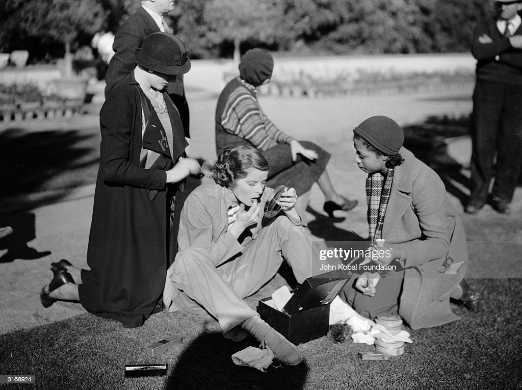 American actress Katharine Hepburn (1907 - 2003) checking her make-up in a park with several members of a film crew, during the making of 'Morning Glory'.