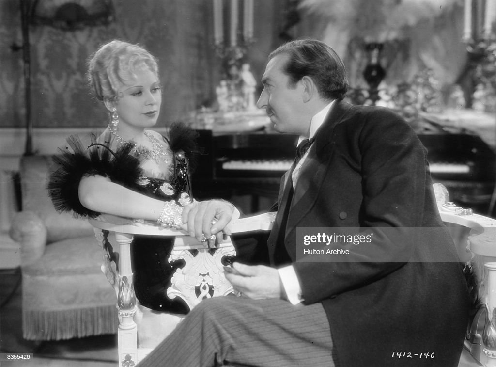 American actress Mae West (1892-1980) shares a love-seat with David Landau (1878-1935) in the Paramount production 'She Done Him Wrong', written by West herself.