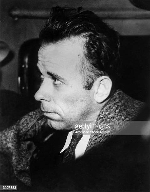 Headshot of American criminal John Dillinger riding in a plane with an escort en route to Indiana to answer charges of murder of a police officer...