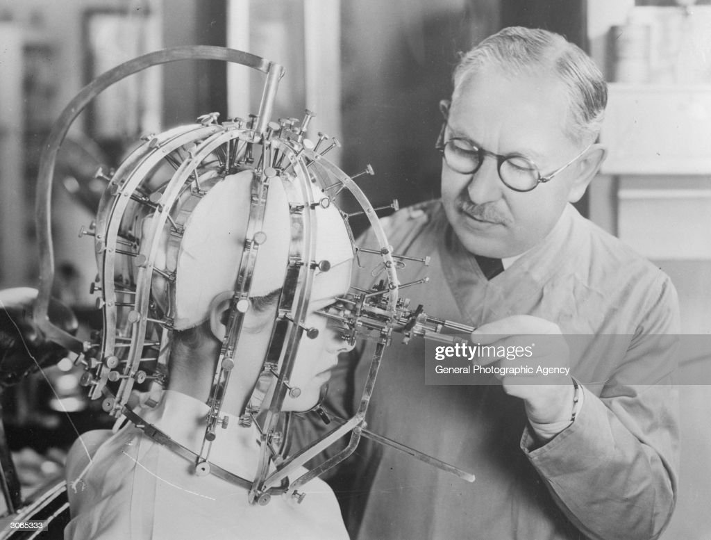 Hollywood cosmetics expert Max Factor (1904 - 1996) takes precise measurements of a young woman's head and face with a contraption like an instrument of torture.