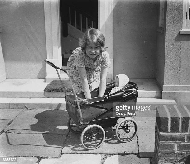 Princess Elizabeth playing with a doll in a toy pram outside the Welsh House a miniature house presented to Princess Elizabeth and Princess Margaret...