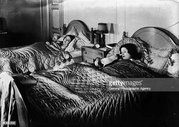 Two girls asleep in their beds with silk quilts and pillows