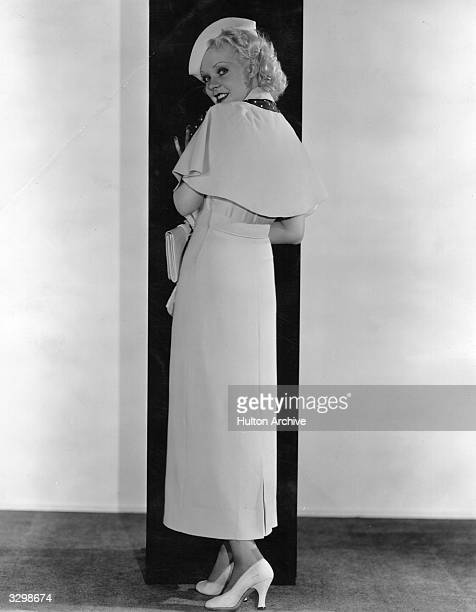 Alice Faye wearing a frock with detachable cape made in heavy white crepe and relieved with navy polkadotted taffeta Other accessories include a tiny...