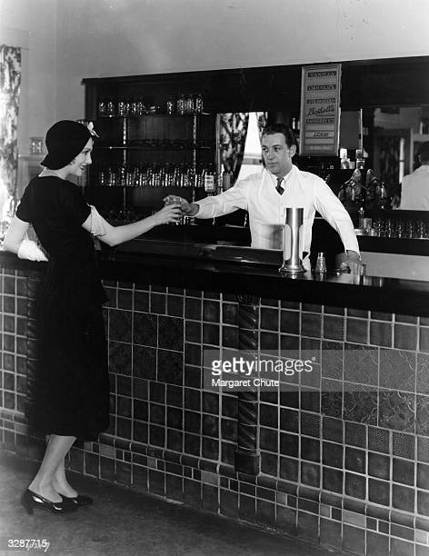 Edwina Booth the MGM Hollywood actress taking her morning orange juice at the studio soda fountain