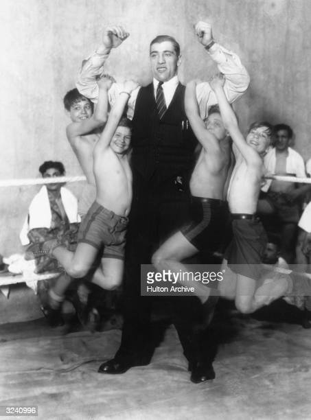 Fulllength image of four boys hanging from American boxer Primo Carnera's arms as he flexes his biceps while standing in the corner of a boxing ring...