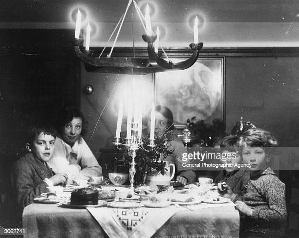 A family at Christmas tea time with chocolate cake a candelabra and holly on the table