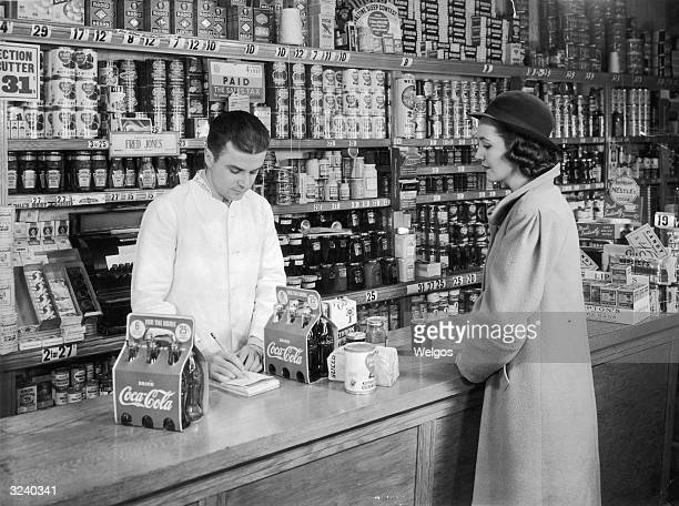 A housewife stands at a grocery counter as the male clerk writes up her bill for two sixpacks of CocaCola bread and canned goods He wears a white...