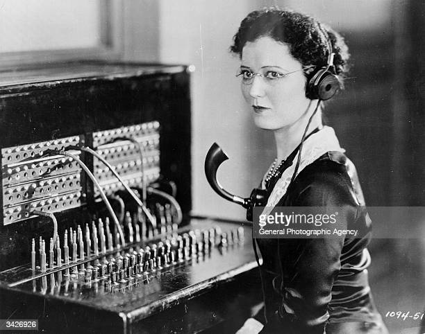 A telephone operator with headphones and a mouthpiece at a switchboard