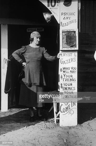 A woman stands with one hand on her hip and the other leaning on a sign advertising 'PSYCHIC LIFE READINGS' with a 'STELLA MAY' sign on a door in the...