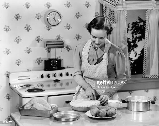 A woman wearing an apron stands behind a kitchen counter preparing a pie crust to be served with a roast turkey and potatoes