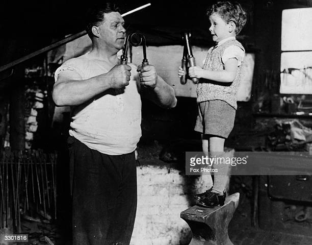 A young boy and his father building up their muscles