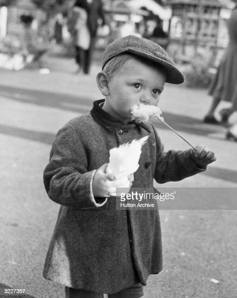 A young boy stands in a city street eating cotton candy from a stick He wears a wool cap and an overcoat